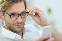 Blonder junger Mann mit Brillen unter Verwendung des Smartphone Stockfotos