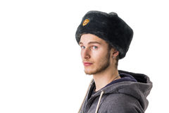 Blonder junger Mann mit russischem Pelzhut Lizenzfreies Stockfoto