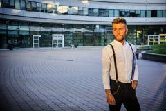 Blonder junger Mann nahe bei modernem Gebäude in der Stadt Lizenzfreie Stockbilder