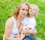 Blonder junger Sohn Mutteramerikanischen nationalstandards, der im Park spielt Stockfotos