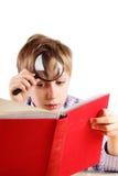 Reizend blonder Junge, der ein helles gebundenes Buch mit einer Lupe liest Lizenzfreie Stockfotografie