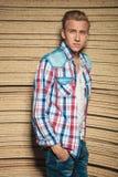 Blonder Kerl, der an der Studiowand mit den Händen in den Taschen sich lehnt Stockfoto