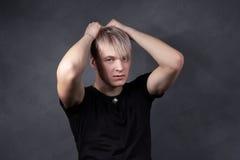 Blonder Kerl mit einem grauen Hintergrund Lizenzfreie Stockbilder