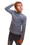 Blonder Kinderjunge in einer gestreiften Strickjacke denkt Stockbild