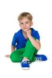 Blonder kleiner Junge in den grünen Hosen sitzt Lizenzfreie Stockfotografie