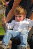 Blonder kleiner Junge, der auf einem Schwingen schwingt Stockbilder