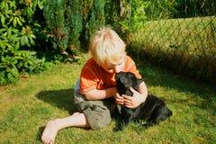 Blonder kleiner Junge, der Hund küßt Stockfotos