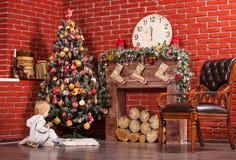 Blonder kleiner Junge, der nahe Weihnachtsbaum spielt Stockbild