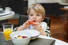 Blonder kleiner Junge, der Pommes-Frites Restaurant im im Freien isst Stockfoto