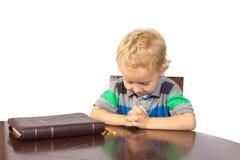 Blonder kleiner Junge, der zum Gott nach dem Ablesen der Bibel betet Stockbild