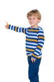 Blonder kleiner Junge hält seinen Daumen hoch Lizenzfreies Stockbild
