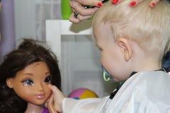 Blonder kleiner Junge schnitt ihr Haar in einem Friseur der Kinder Stockfotografie