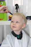 Blonder kleiner Junge schnitt ihr Haar in einem Friseur der Kinder Stockbild