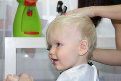 Blonder kleiner Junge schnitt ihr Haar in einem Friseur der Kinder Lizenzfreie Stockfotos