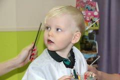 Blonder kleiner Junge schnitt ihr Haar in einem Friseur der Kinder Lizenzfreie Stockfotografie