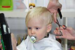 Blonder kleiner Junge schnitt ihr Haar in einem Friseur der Kinder Lizenzfreies Stockbild