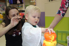 Blonder kleiner Junge schnitt ihr Haar in einem Friseur der Kinder Stockfoto