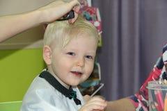 Blonder kleiner Junge schnitt ihr Haar in einem Friseur der Kinder Lizenzfreie Stockbilder
