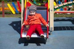 Blonder kleiner Junge sitzt auf einem Dia der Kinder am Spielplatz Stockfoto