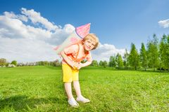 Blonder kleiner Junge trägt Raketenspielzeug auf seinen Schultern Stockbild