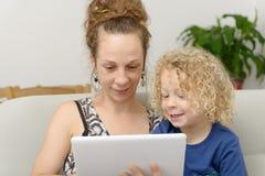Blonder kleiner Junge und seine Mutter mit einer digitalen Tablette Lizenzfreie Stockfotografie