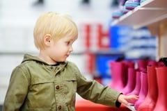 Blonder kleiner Junge während des Einkaufens mit Eltern Stockbild