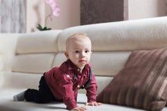 Blonder Kleinkindjunge auf dem Sofa Lizenzfreie Stockfotos