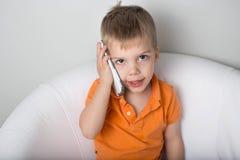 Blonder Kleinkindjunge, der auf dem Telefon und dem Lächeln spricht Lizenzfreie Stockfotos