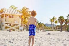 Blonder Kleinkindjunge, der Spaß auf Miami Beach, Key Biscayne hat Glückliches gesundes nettes Kind, das mit Sand und Betrieb spi stockfotografie