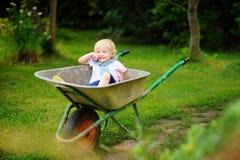 Blonder Kleinkindjunge, der Spaß in einer Schubkarre hat Stockfotos