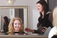 Blonder Kunde des Herrenfriseurhaarsprays im Friseursalon Lizenzfreie Stockfotografie