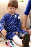 Blonder lächelnder Griff des kleinen Mädchens in der Armbürste Stockbild