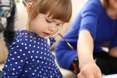 Blonder lächelnder Griff des kleinen Mädchens in der Armbürste Lizenzfreies Stockfoto
