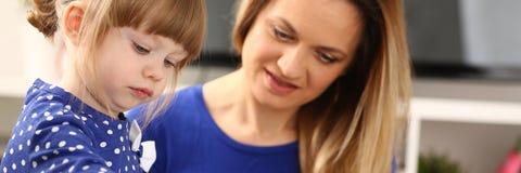 Blonder lächelnder Griff des kleinen Mädchens in der Armbürste Lizenzfreie Stockfotografie