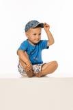 Blonder lächelnder Junge, der auf dem Tisch tragende Baseballmütze sitzt Lizenzfreie Stockbilder