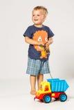 Blonder lächelnder Junge, der mit einem Plastikauto spielt, Stockfoto