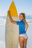 Blonder lächelnder Surfer, der ihr Brett auf dem Strand hält Stockbilder