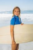 Blonder lächelnder Surfer, der ihr Brett auf dem Strand hält Lizenzfreie Stockfotografie