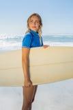 Blonder lächelnder Surfer, der ihr Brett auf dem Strand hält Lizenzfreie Stockfotos