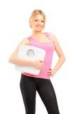 Blonder lächelnder weiblicher Athlet, der eine Gewichtsskala anhält Stockfotos