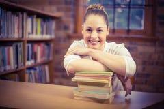 Blonder Lehrer, der auf Stapel von Büchern in der Bibliothek sich lehnt Stockfotografie