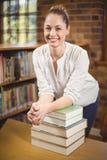 Blonder Lehrer, der auf Stapel von Büchern in der Bibliothek sich lehnt Lizenzfreie Stockfotos
