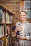 Blonder Lehrer, der Bücher in der Bibliothek hält Stockbilder