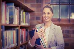 Blonder Lehrer, der Bücher in der Bibliothek hält Lizenzfreie Stockfotografie