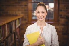 Blonder Lehrer, der Buch in der Bibliothek hält Lizenzfreie Stockfotografie