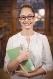 Blonder Lehrer, der Buch in der Bibliothek hält Lizenzfreies Stockbild