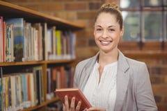 Blonder Lehrer, der Buch in der Bibliothek hält Stockfotografie