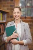 Blonder Lehrer, der Buch in der Bibliothek hält Stockbilder