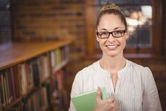 Blonder Lehrer, der Buch in der Bibliothek hält Lizenzfreie Stockbilder