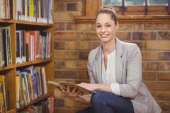 Blonder Lehrer, der Buch in der Bibliothek sucht Stockbilder
